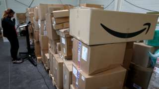 An employee prepares an order for Amazon at Porona warehouse in Bruay-sur-l'Escaut near Valenciennes, France, April 22, 2020