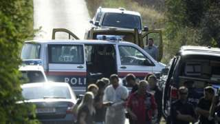 Austrian police are seen near the Austrian-Hungarian border near Siegendorf, Burgenland, Eisenstadt district, on October 19, 2021, where two migrants were discovered dead inside a van (yellow vehicle) during a control.