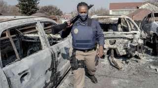 - A Johannesburg Metro Police Department (JMPD) officer walks between burnt cars at a car showroom in Jeppestown, Johannesburg, on July 11, 2021.