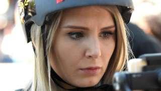 Lauren Southern, wearing a helmet, filming a crowd on a smart phone.