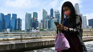 Woman on mobile phone in front of Singapore skyline
