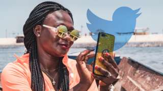 A woman in Ghana using a phone with the Twitter logo in the background