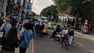 the scene close to where a man has been stabbed to death on a busy street