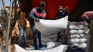 Pessoas carregam sacos de comida do Programa Mundial de Alimentos
