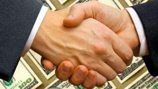 Dos hombres se dan la mano con un fondo de dólares