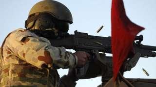 An unidentified Australian soldier test fires a gun
