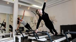 An instructor and gym member wear face masks as they take part in a pilates session at Fernwood Fitness Annadale gym, following 108 days of lockdown in Sydney, New South Wales, Australia, 11 October 2021