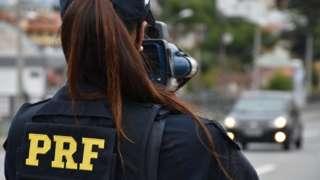 Agente da PRF, identificada por colete e boné, usa equipamento de fiscalização em estrada