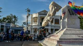 rotestors topple a statue of Christopher Columbus during a demonstration against government in Barranquilla, Colombia on June 28, 2021.
