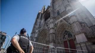 A police officer stares up at the charred front of the cathedral in Nantes