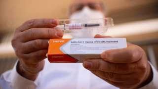 Homem segura embalagem e ampola da vacina produzida pela Sinovac