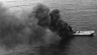 Imagem aérea e em preto e branco de navio queimando no meio do mar