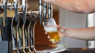 A barman pours a pint of beer in a bar