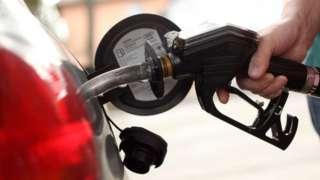 Una persona llena su tanque de gasolina