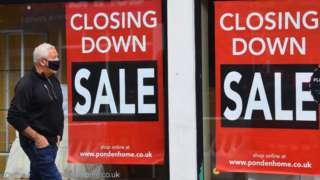 Man walking past a shop that is closing down