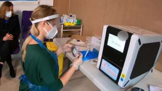 Care home staff member with test machine