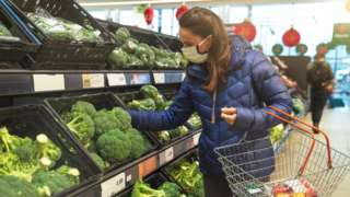 Woman wearing a face mask in a supermarket