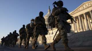 Soldiers walk in a line outside Capitol