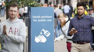 man uses a public hand sanitiser in Leeds city centre