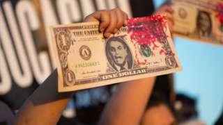 Protesto com nota falsa de dólar e manchada de sangue falso