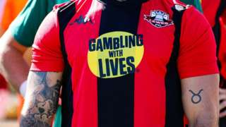 Close up image of a footballer in a red and black striped Lewes FC football shirt with a logo on the front.