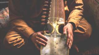 afghan person holding instrument