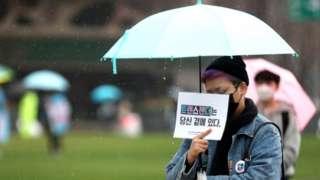 서울광장에서 열린 '변희수 하사를 기억하며-트랜스젠더 가시화의 날 공동 기자회견'에서 참석자들이 손팻말을 들고 기자회견을 지켜보고 있다