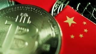 Metalna kovanica sa znakom bitkoina stoji na stolu pored malih zastava Kine