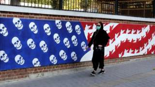 An Iranian woman walks past a mural painted on the outer walls of the former US embassy in Tehran, Iran (4 November 2020), on November 4, 2020 as the US waits for the results of the presidential election