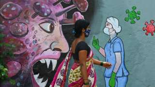 A pedestrian walks past a wall mural depicting a frontline medical staff stopping the Covid-19 coronavirus, in Navi Mumbai in June.