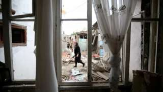 Woman walks past house damaged by shelling in the Azerbaijani city of Ganja - 6 October