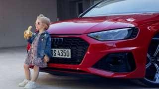 طفلة تتكئ على سيارة أودي