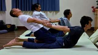 Thai instructor (centre L) trains her students from Chile (centre R), France (front R) and a Thai (front L) at the Wat Po Thai traditional massage school,