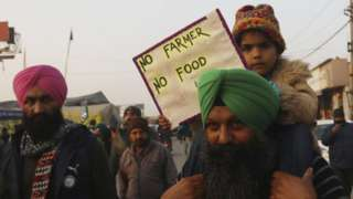 A child on a adult's shoulders holding a sign saying 'no farmer no food'
