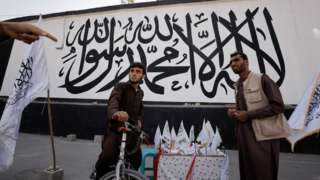 Men react while they sell Taliban flags of the Islamic Emirate of Afghanistan in front of a mural with the same flag, in front of the former U.S. embassy in Kabul, Afghanistan October 8, 2021.