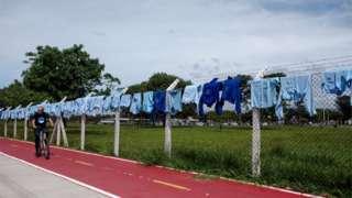 Dezenas de camisas de trabalho penduradas em cerca de fábrica