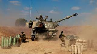 Israeli soldiers fire towards the Gaza Strip on 13 May