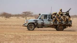 Burkina Faso soldiers patrol aboard a pick-up truck on the road from Dori to the Goudebo refugee camp, on February 3, 2020