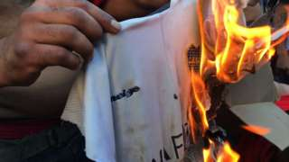 A River Plate fan sets a Boca Juniors shirt alight