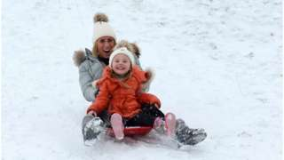 A woman and child sledging down a hill