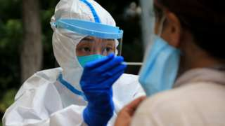 """A healthcare worker carries out a Covid-19 test in Dalian, in China""""s northeast Liaoning province"""