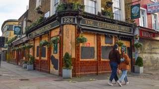 Couple walk past closed pub in Camden, London
