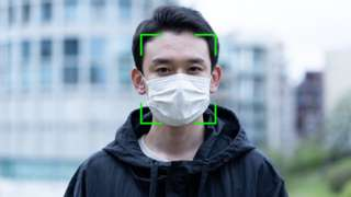 Man wearing a face mask with facial recognition overlayed