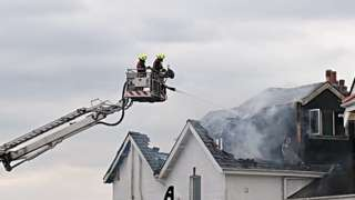 Firefighters tackle the fire with water spray