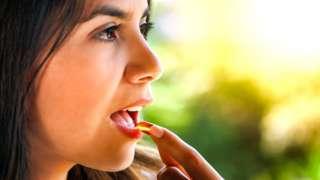 Woman taking vitamin D capsule