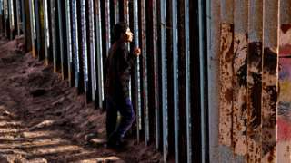 A man looks on through the US-Mexico border wall in Playas de Tijuana, northwestern Mexico in November 2018
