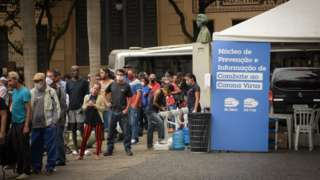 Pessoas se aglomeram em fila para receber refeição distribuída por padres franciscanos no largo São Francisco, no centro de São Paulo
