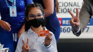 A student holds a National Vaccination Plan card when receiving a dose of the Sinovac vaccine as part of the immunization plan against COVID-10 for children aged 6 to 11 at Alicante del Rosal school on October 1, 2021 in Santiago, Chile.