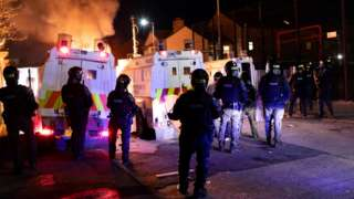 Police in riot gear watch as a car burns in front of police Land Rovers in Belfast