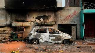 A burnt-out vehicle is pictured following clashes between people supporting and opposing a contentious amendment to India's citizenship law, in New Delhi on February 26, 2020